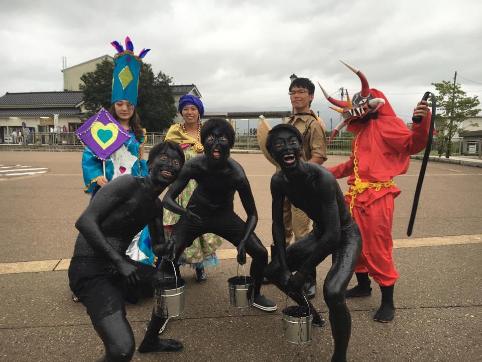 パレード開始直前、スタート地点の福野駅前にてEK仮装隊。後列左から、お姫さま(ファンタシア)、仏領カリブ風マダム(マダマ)、金鉱夫(ミネーロ)、悪魔(ディアブロ)。前列には3人のメディオピント。