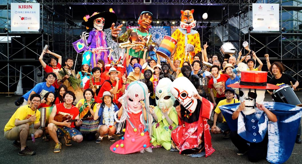 パレード終了後、ゴール地点の「ヘリオスステージ」前での全体集合写真。最後列に巨大人形、最前列に髑髏ダンサーたち。